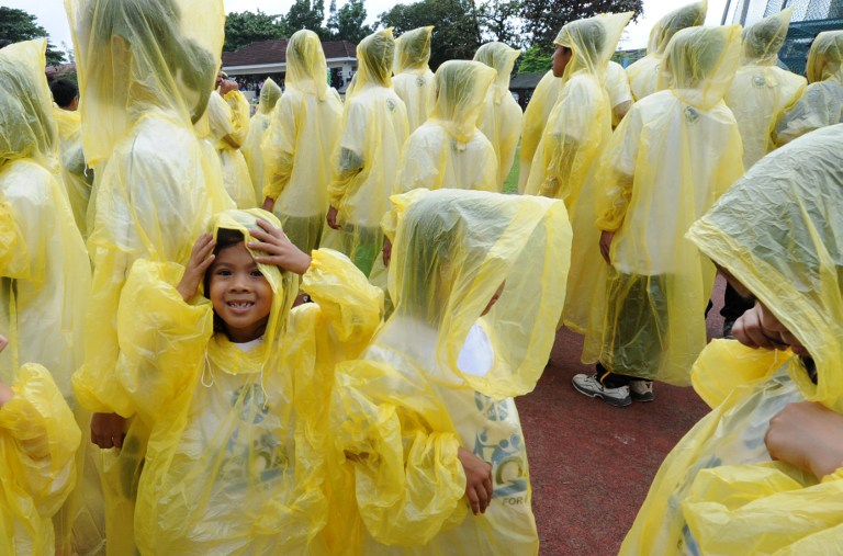 HELLO, RAIN. Filipino school children wearing raincoats during an event in Pasig city, September 2, 2012. File photo by Jay Directo/AFP
