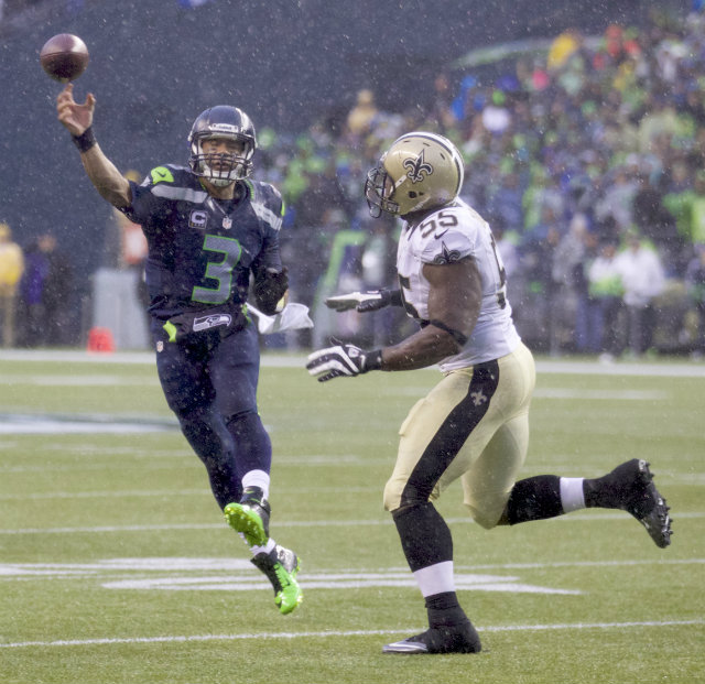 HAWK TIME. Seattle Seahawks quarterback Russell Wilson passes the ball as New Orleans Saints defensive end Keyunta Dawson defends in the second half of their NFL Divisional playoff game at CenturyLink Field in Seattle, Wash. on Saturday, January 11. The Seahawks won 23-15 to advance to the NFC Championship game. Photo by Stephen Brashear/EPA