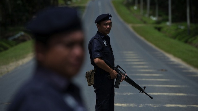 MILITANTS SURROUNDED. Malaysian armed policemen man a security check in Sahabat 7 on the road leading to Tanjung Tanduo, in the areas where suspected Philippine militants are holding off on the Malaysian island of Borneo on February 18, 2013. AFP PHOTO / MOHD RASFAN
