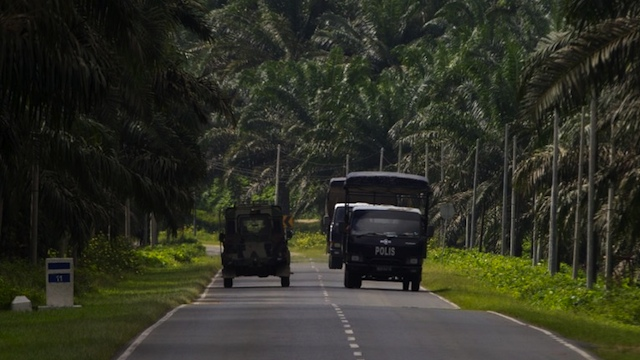 DEADLY STANDOFF. Malaysian police (R) and an army truck drive past each other in Lahad Datu on the Malaysian island of Borneo on March 3, 2013. AFP PHOTO / MOHD RASFAN