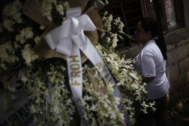 THE WIDOW. Lilibeth Natividad stands watch over her husband's coffin. 9 June 2013.