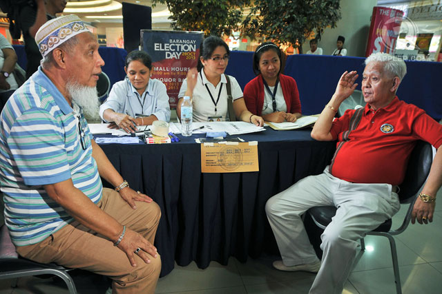 SENIORS, TOO. Comelec chairman Sixto Brillantes Jr and Commissioner Elias Yusoph arrive at the special polling center for PWDs and senior citizens at SM Manila. Photo by Roy Lagarde