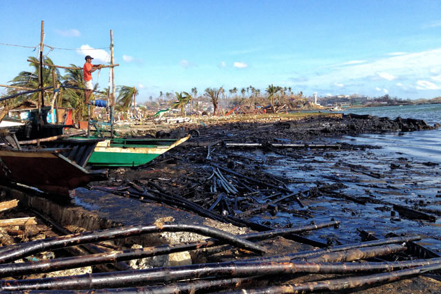 COVERED IN OIL. Logs and other pieces of wood covered along the shoreline of Barangay Botongon in Estancia town. File photo by Jonathan Jurilla, Typhoon Yolanda Story Hub Visayas