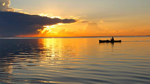 A boat glides on Siargao water