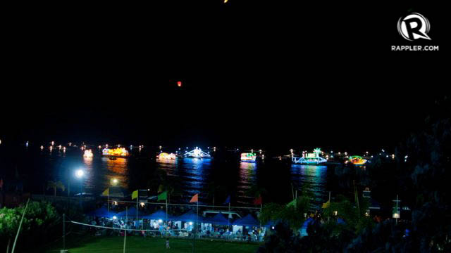 SEA SPECTACLE. Colorful boats all aglow for the night show
