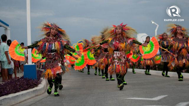 STREET DANCERS. Smiling performers decked in body paint, feathers, and colorful costumes perform in the street dancing competition