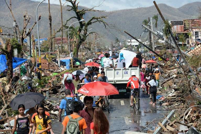 DECIMATED. Residents walk through debris and toppled power lines in Tacloban City, Leyte on November 10, 2013, three days after devastating Typhoon Yolanda (Haiyan) hit the city on November 8. AFP/Ted Aljibe