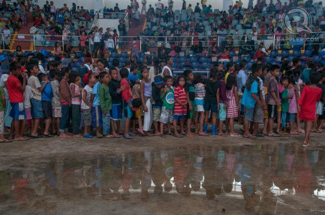 EVACUATING AGAIN. Hundreds of Yolanda (Haiyan) survivors, who still live in tents, return to the Tacloban Astrodome as Glenda (Rammasun) is set to affect Tacloban City. Photo by Roy Lagarde/Rappler