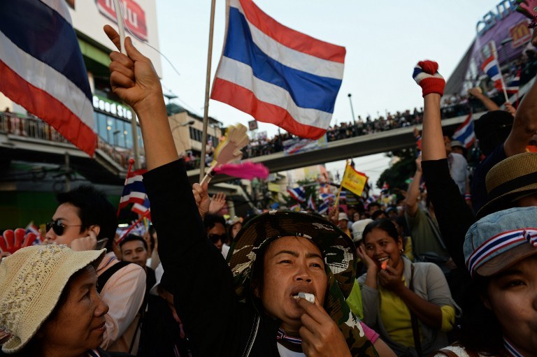 UNREST IN BANGKOK. Thai anti-government protesters wave national flags and blow whistles as they rally at Victory Monument in Bangkok as part of their ongoing rally on December 22, 2013. AFP/Christophe Archambault
