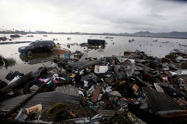 DEVASTATION. A man searches for belongings washed ashore by the typhoon that devastated the city of Tacloban. Photo by EPA/Dennis Sabangan