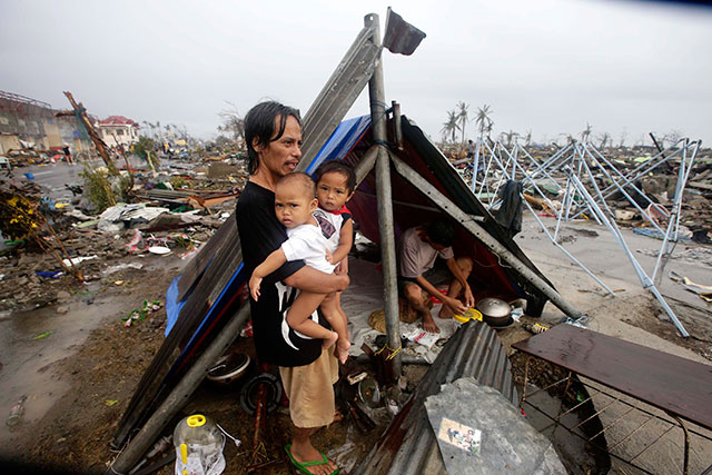 WAITING. Calamity victims wait for food relief outside their makeshift tent in Tacloban city. Photo by EPA/Dennis Sabangan
