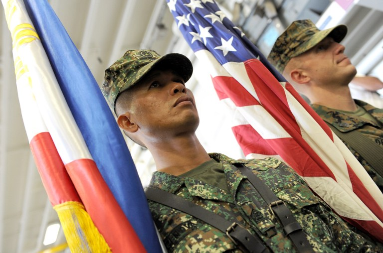SIDE BY SIDE. US and Philippine Marines carry their respective colors at the formal opening of the annual Philippine-US Amphibious Landing Exercises aboard the USS Bonhomme Richard which docked at the former US naval base of Subic on October 8, 2012. File photo by AFP/Jay Directo